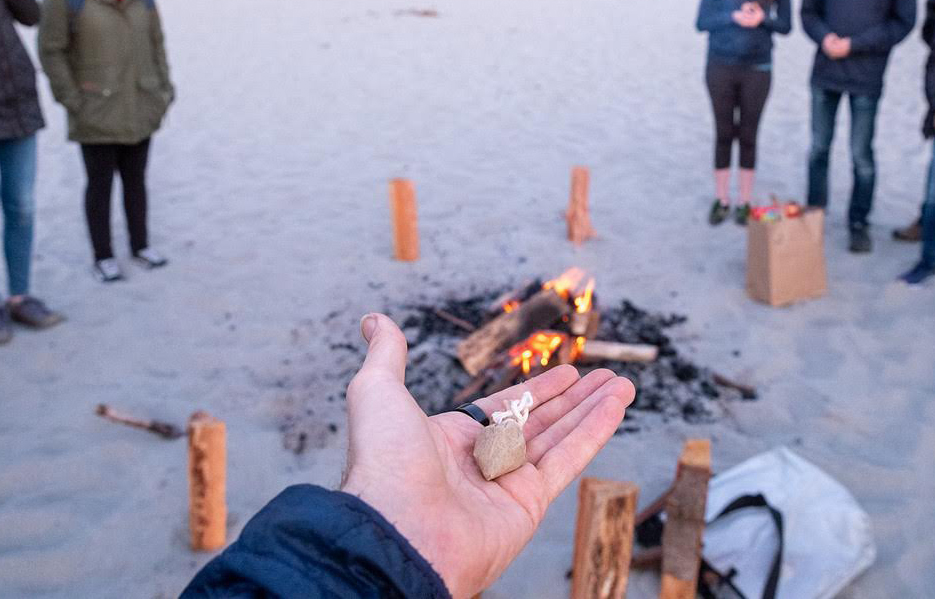 a hand holding an offering in front of a bonfire
